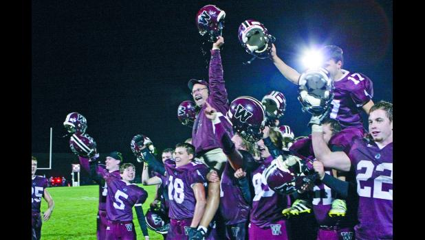 Winamac head coach Tim Roth is lifted by his players after the Warriors beat Bremen 21-14 for the sectional championship.