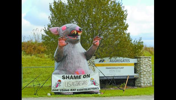 """Scabby the Rat was recently seen holding a banner that accused U.S. Aggregates of using """"rat contractors."""""""