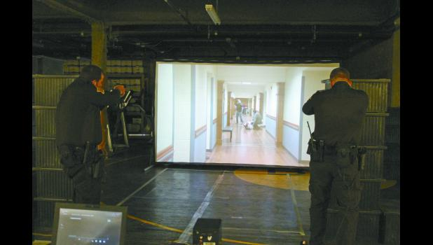 Pulaski County Sheriff's Deputy Matt Pickens and reserve deputy and jail Sgt. Chris McAninch train with the scenario simulator on Nov. 1. This is the first time they have participated in the scenario with the sheriff's office.