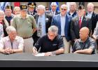 Gov. Eric Holcomb (seated, center) signs legislation co-authored by State Rep. Doug Gutwein (R-Francesville) (first row standing, far left) providing tax relief to many Hoosier veterans Monday, Aug. 5, at the Indiana State Fair in Indianapolis. The new law will phase in a full income tax exemption for military retirement pensions over four years, helping to support the hard-earned benefits of Hoosier veterans.